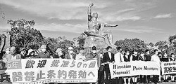 (写真)横断幕を掲げる被爆者5団体と高校生1万人署名活動のメンバーら=25日、長崎市