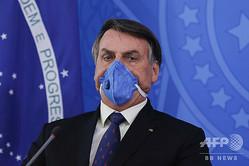 ブラジル・ブラジリアで、マスクを着用して記者会見に臨むジャイル・ボルソナロ大統領(2020年3月20日撮影)。(c)Sergio LIMA / AFP