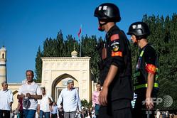 中国・新疆ウイグル自治区カシュガルで、モスクでの礼拝を終えたウイグル人らを見張る警察官(2017年6月26日撮影)。(c)Johannes EISELE / AFP