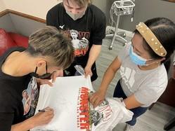 ボクシングファンの看護師(右)にプレゼンするTシャツにサインする井上尚弥(大橋ジム提供)