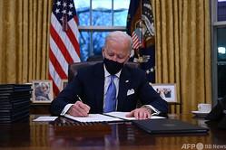 米ホワイトハウスの大統領執務室で、複数の大統領令に署名するジョー・バイデン新大統領(2021年1月20日撮影)。(c)Jim WATSON / AFP