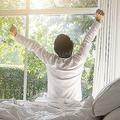 新鮮な気持ちで朝ウィンドウに手を上がってベッドで目覚める幸せな怠け者リラックス