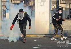 イラクの首都バグダッドのタヤラン広場で、治安部隊が発射した催涙ガスのキャニスターをつかんだデモ参加者(2020年1月20日撮影)。(c)AHMAD AL-RUBAYE / AFP