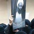 サウジアラビア東部カティーフで、イスラム教シーア派指導者ニムル・ニムル師の肖像を掲げ、同師の死刑執行に抗議する女性(2016年1月8日撮影、資料写真)。(c)AFP=時事/AFPBB News