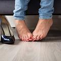 Close-up Of A Woman's Leg Near High Heels On Hardwood Floor