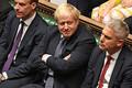 19日、ロンドンの英下院で、笑みを浮かべるジョンソン首相(中央)=議会提供(AFP時事)