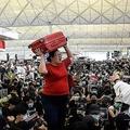 香港空港で、荷物を頭上に持ち上げて出発ゲートへ進もうとする旅行者(2019年8月13日撮影)。(c)Philip FONG / AFP