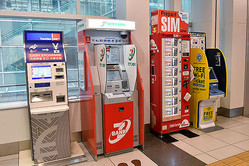 2016年6月13日、羽田空港の国際線到着ロビーに設置された、(左から)外貨両替機、セブン銀行のATM、プリペイドSIMの販売機、フリーWi−Fiのチケット販売機(東京都大田区)(写真=時事通信フォト)