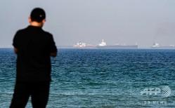 ビーチに立ち、アラブ首長国連邦(UAE)フジャイラ沖のオマーン湾にいるタンカーを見る男性(2019年6月15日撮影)。GIUSEPPE CACACE / AFP